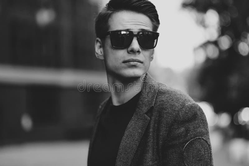 Individuo fresco serio con las gafas de sol que camina en la calle imagen de archivo