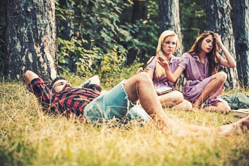 Individuo fuerte que miente en hierba Dos libros de lectura de las muchachas al lado de la hoguera Amigos que acampan en verano imagen de archivo libre de regalías