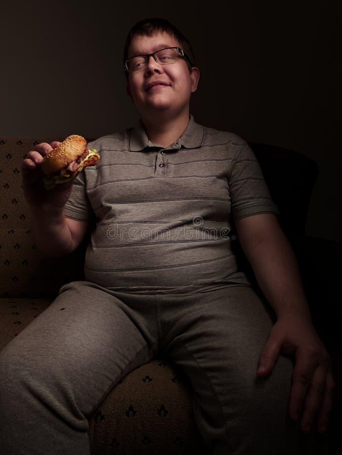 Individuo gordo solo que come la hamburguesa Malos hábitos alimentarios foto de archivo