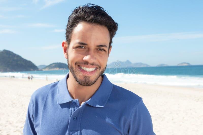Individuo hermoso con la barba y camisa azul en la playa fotografía de archivo