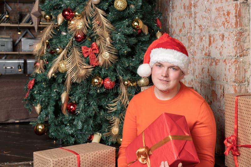 Individuo hermoso en caja de la tenencia del sombrero de Papá Noel con el regalo que se sienta debajo del árbol rodeado por las c fotos de archivo