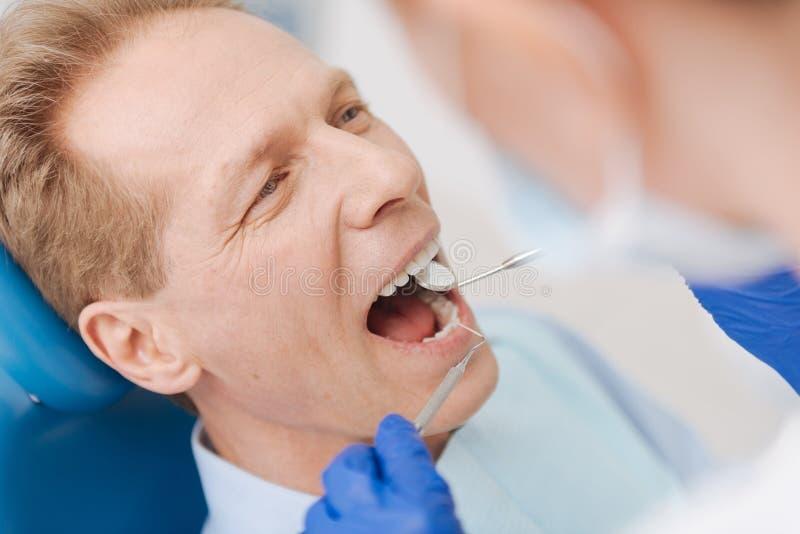 Individuo hermoso envejecido centro que hace sus dientes comprobar fotos de archivo