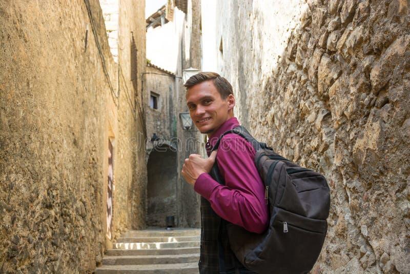 Individuo hermoso joven con una mochila que sonríe, caminando a lo largo del fotografía de archivo libre de regalías