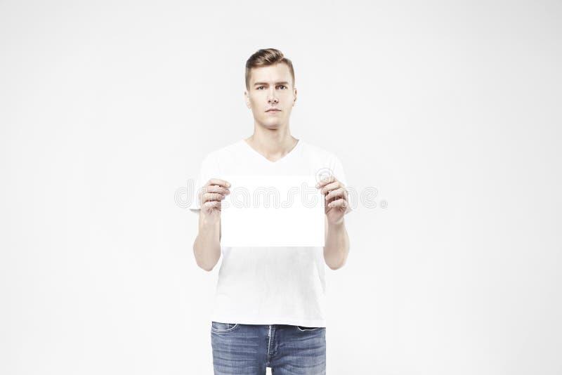 Individuo hermoso que se coloca con la hoja en blanco a disposición, aislado en el fondo blanco, vaqueros que llevan y la camiset imágenes de archivo libres de regalías