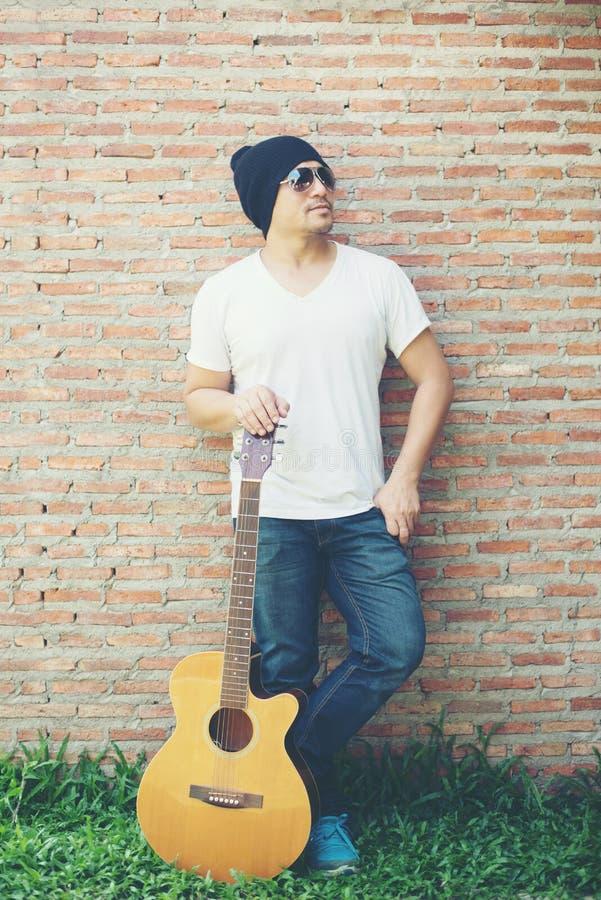 Individuo hermoso que se coloca que sostiene la guitarra contra el posi de la pared de ladrillo imagen de archivo