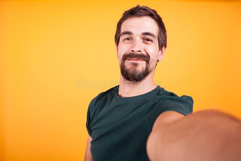 Individuo hermoso sonriente fresco que sonríe en la cámara mientras que toma un selfie fotos de archivo libres de regalías