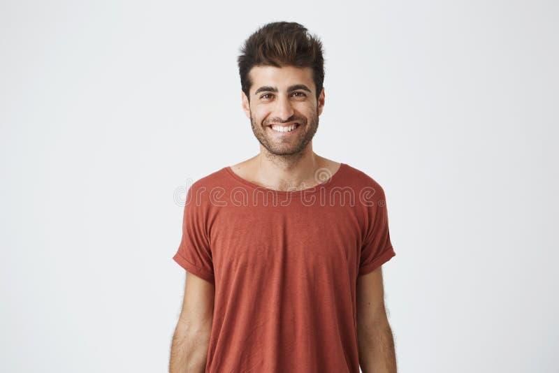 Individuo hispánico alegre joven en noticias brillantemente sonrientes rojas de la audición de la camiseta buenas del amigo Estud fotografía de archivo libre de regalías