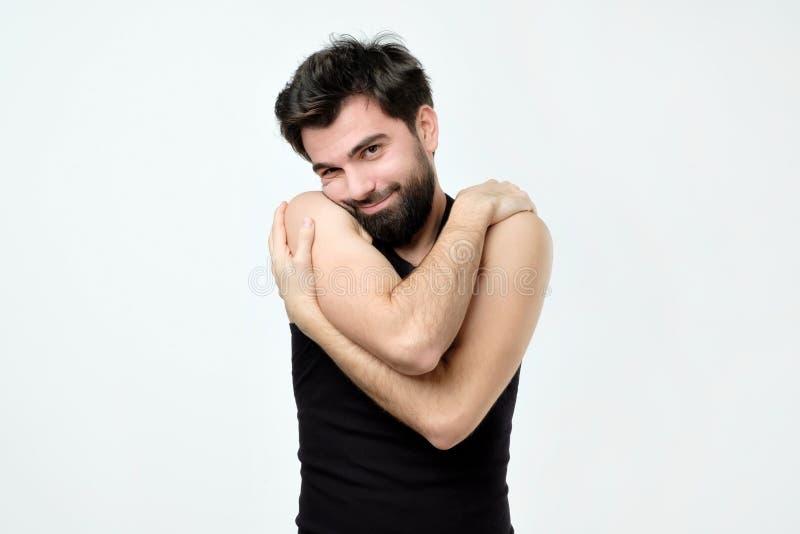 Individuo hispánico egoísta divertido en camisa negra que se abraza y la sonrisa imagen de archivo