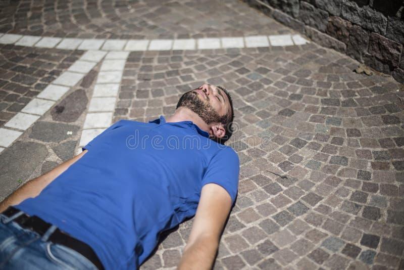 Individuo inconsciente en el piso foto de archivo libre de regalías