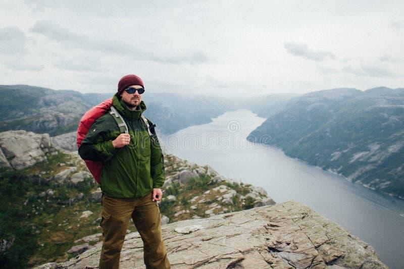 Individuo joven con la mochila que disfruta de puesta del sol en pico del mountai de niebla fotografía de archivo