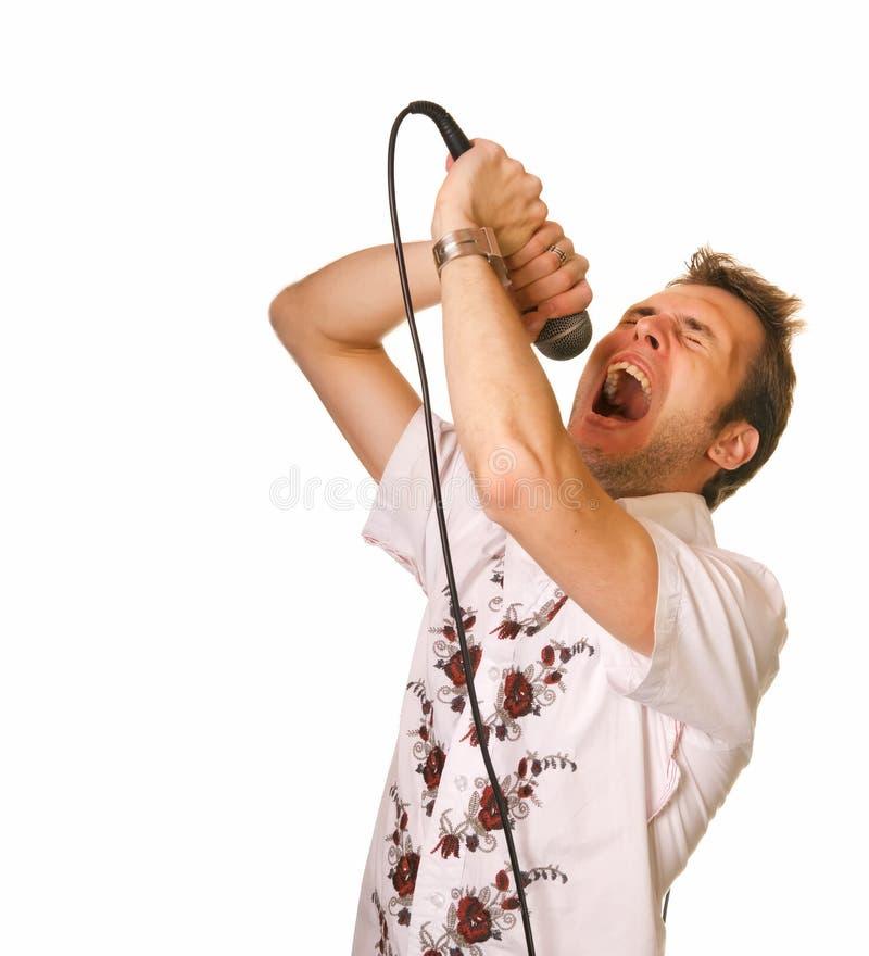 Individuo joven con un micrófono foto de archivo