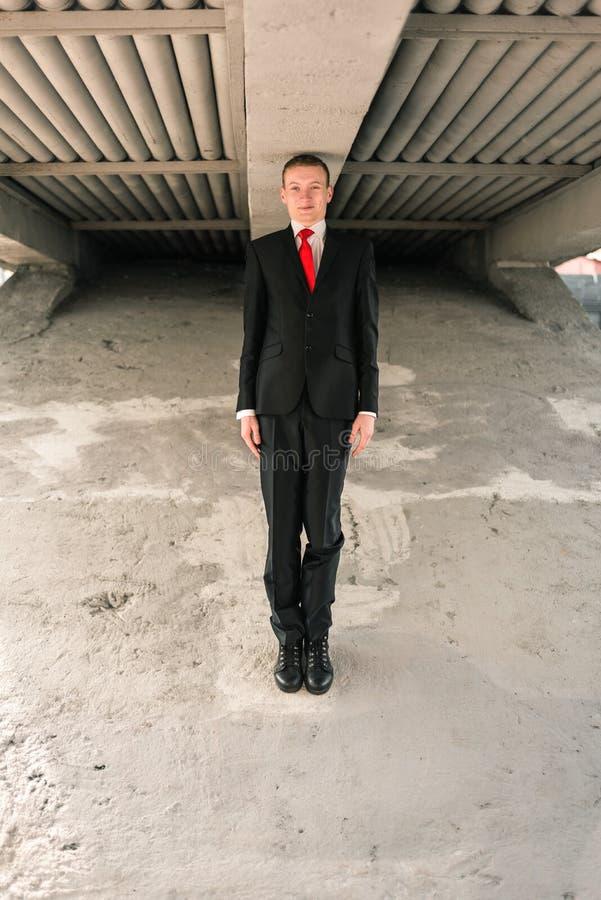 Individuo joven divertido en un traje negro y un lazo rojo El hombre alto se coloca debajo del puente fotografía de archivo