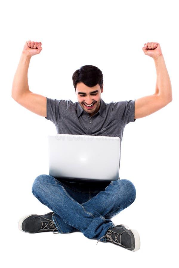 Individuo joven emocionado con el ordenador portátil foto de archivo