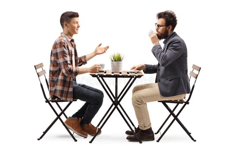 Individuo joven en un café que habla con un café de consumición del hombre barbudo fotografía de archivo