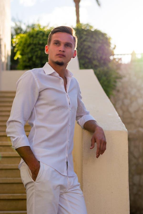 Individuo joven en una camisa blanca y soportes de las gafas de sol cerca de las escaleras y de las flores en la puesta del sol imagenes de archivo