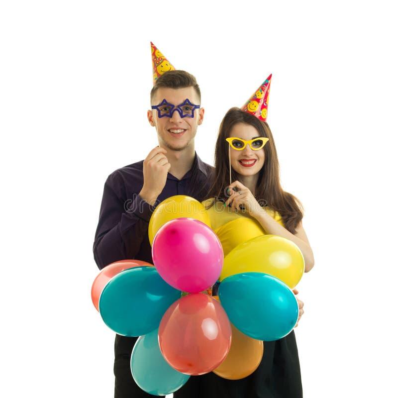 Individuo joven gay con una muchacha, sosteniéndose cerca de los vidrios del papel del ojo y de las porciones de globo coloreado  foto de archivo libre de regalías