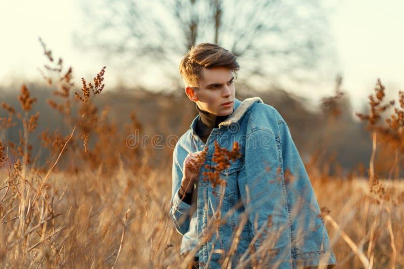 Individuo joven hermoso con una camisa de la chaqueta y del dril de algodón de la moda de los vaqueros imagenes de archivo
