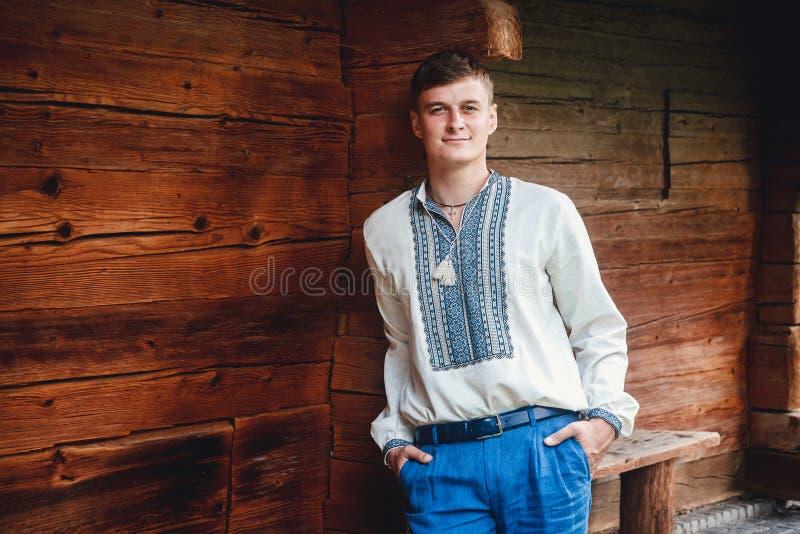 Individuo joven hermoso en una camisa bordada en el fondo de una casa de madera imágenes de archivo libres de regalías