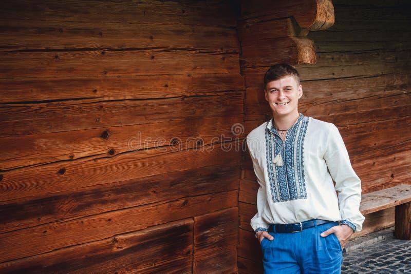 Individuo joven hermoso en una camisa bordada en el fondo de una casa de madera imagen de archivo libre de regalías