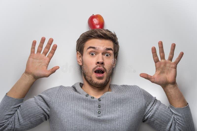 Individuo joven hermoso que equilibra la manzana roja en su cabeza fotos de archivo
