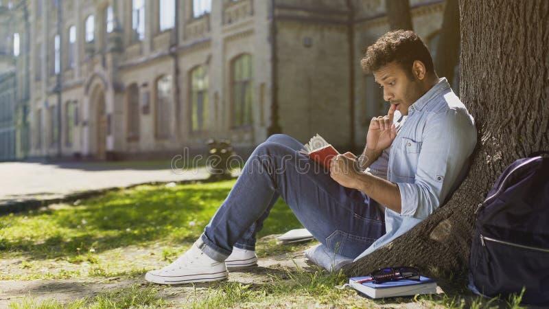 Individuo joven multirracial que se sienta debajo del árbol, leyendo el libro interesante, ratón de biblioteca fotografía de archivo libre de regalías