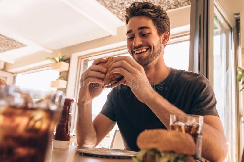Individuo joven que apila la hamburguesa fotos de archivo