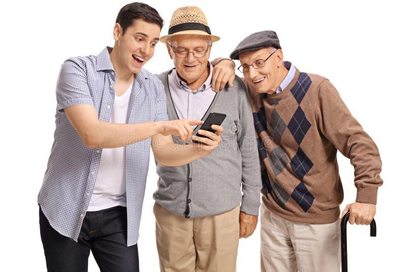 Individuo joven que muestra algo en el teléfono a dos hombres mayores imagen de archivo libre de regalías