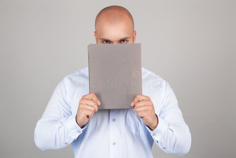 Individuo joven que sostiene un libro delante de su cara mientras que lleva una camisa azul, colocándose en el fondo blanco del e fotos de archivo