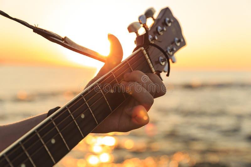 Individuo joven que toca una guitarra en la puesta del sol imagen de archivo libre de regalías