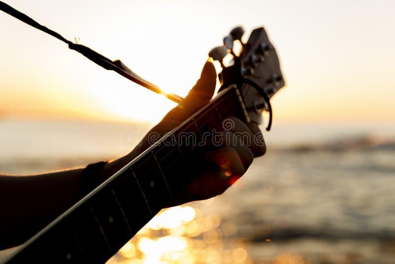 Individuo joven que toca una guitarra en la puesta del sol fotografía de archivo libre de regalías
