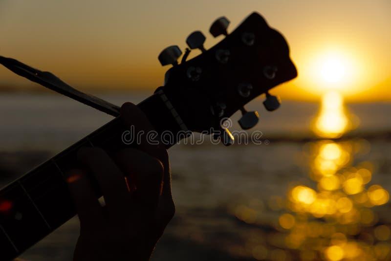 Individuo joven que toca una guitarra en la puesta del sol imágenes de archivo libres de regalías