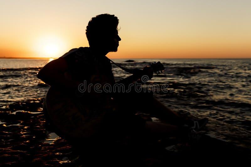 Individuo joven que toca una guitarra en la puesta del sol fotografía de archivo