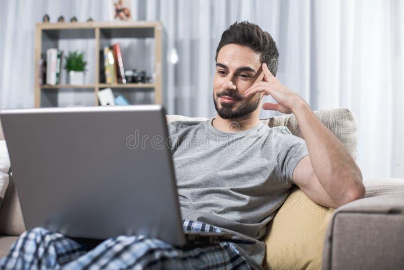 Individuo joven sereno con el ordenador portátil foto de archivo libre de regalías