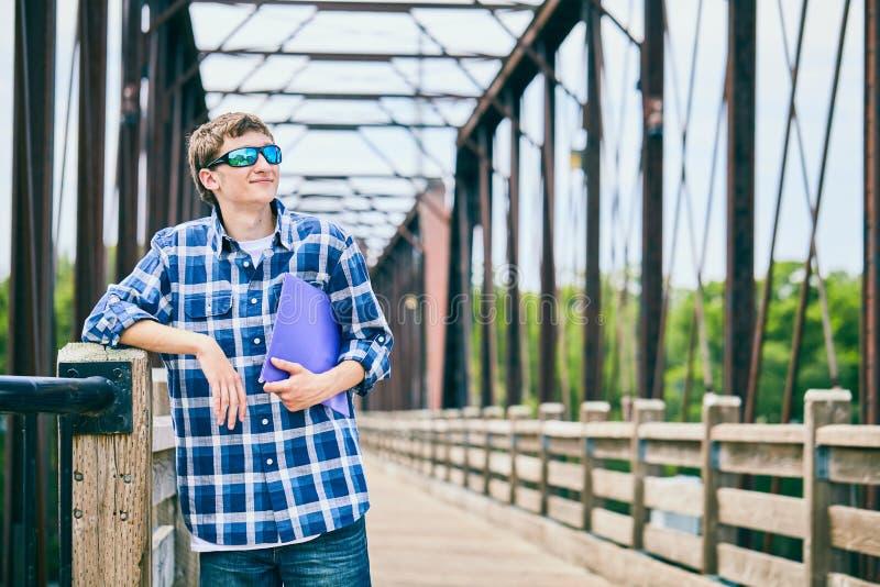 Individuo joven sonriente en las gafas de sol que sostienen la carpeta fotos de archivo libres de regalías