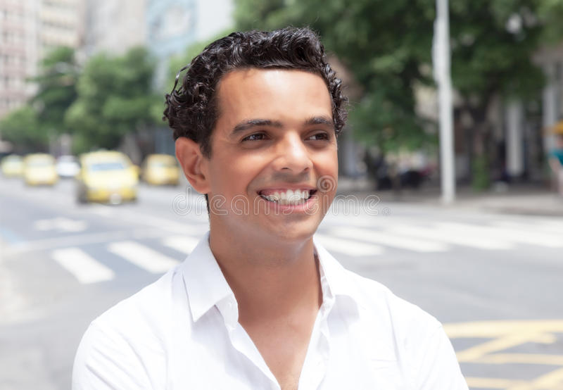 Individuo latino de risa que busca un taxi en la ciudad foto de archivo libre de regalías