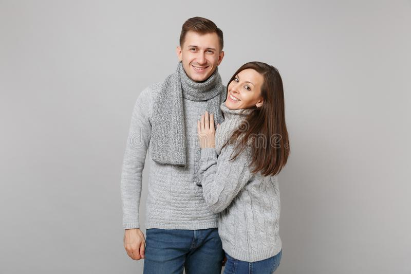 Individuo lindo joven de la muchacha de los pares en los suéteres grises, bufandas juntas aisladas en el fondo gris de la pared,  imagen de archivo