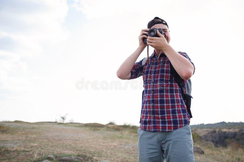 Individuo lindo que camina y que toma imágenes con la cámara El caminar en las montañas con una cámara El mejor pasatiempo del ve imagen de archivo libre de regalías