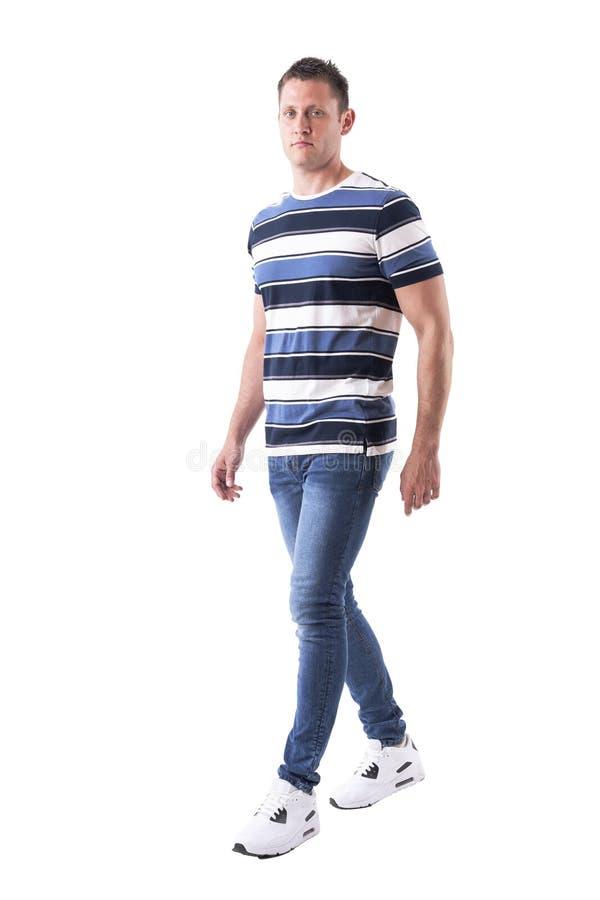Individuo machista confiado en ropa casual que camina y que mira la cámara imagen de archivo