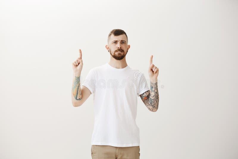 Individuo maduro apuesto con la barba y tatuajes en los brazos, aumentando los dedos índices y señalando hacia arriba con dudoso  foto de archivo