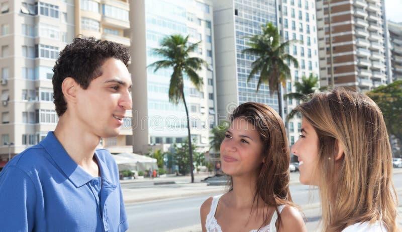 Individuo mexicano joven que habla con dos novias en la ciudad imágenes de archivo libres de regalías