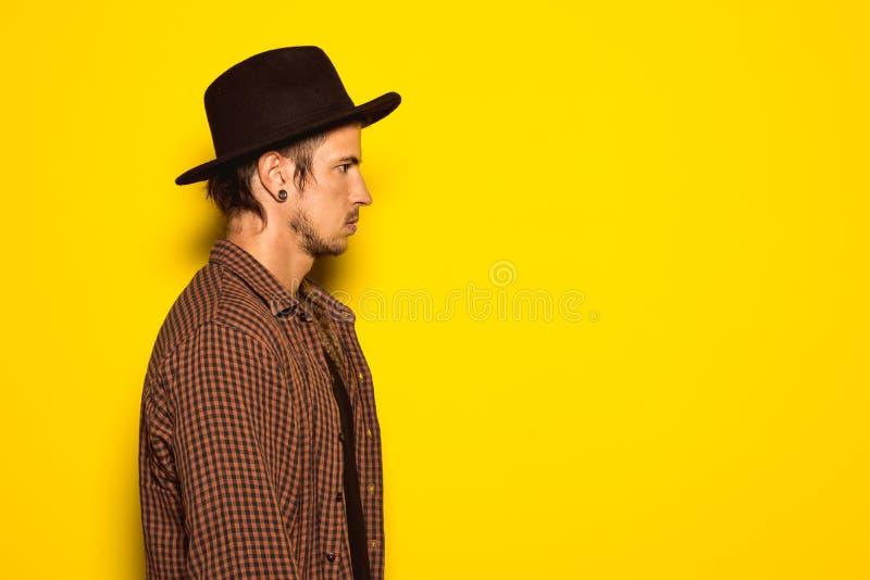 Individuo moderno y hermoso con un sombrero negro en un fondo amarillo fotografía de archivo libre de regalías