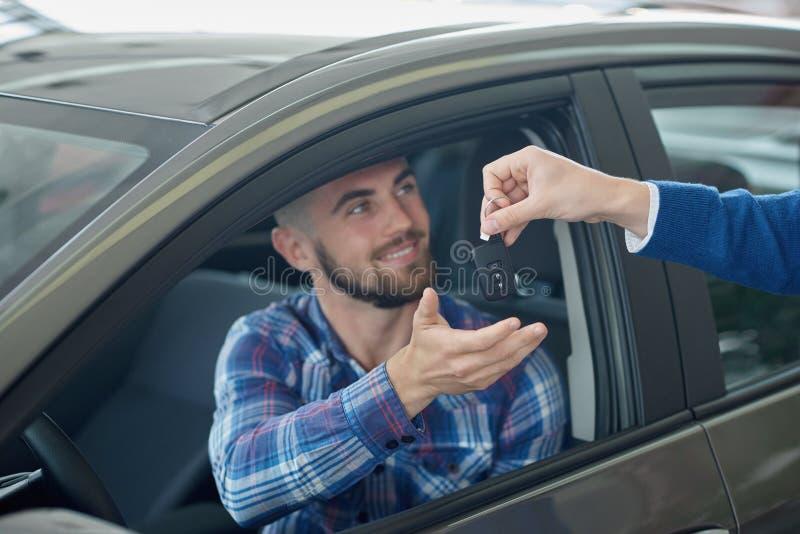 Individuo moreno que consigue dominante de encargado después de comprar el vehículo fotos de archivo libres de regalías