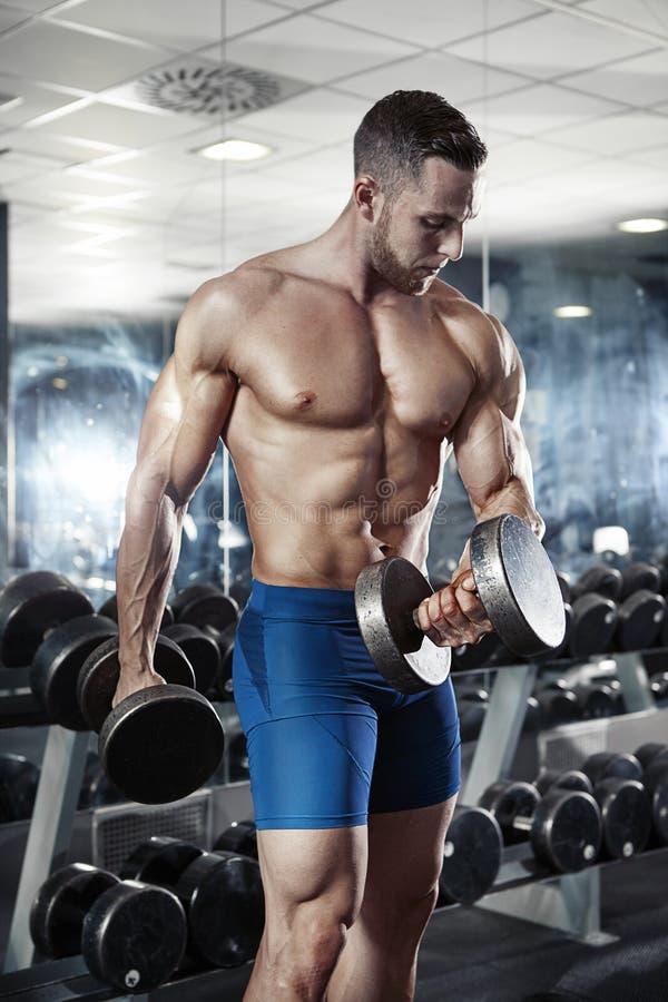 Individuo muscular del culturista que hace ejercicios con pesa de gimnasia fotografía de archivo