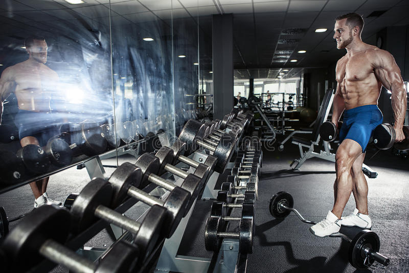 Individuo muscular del culturista que hace ejercicios con pesa de gimnasia imágenes de archivo libres de regalías