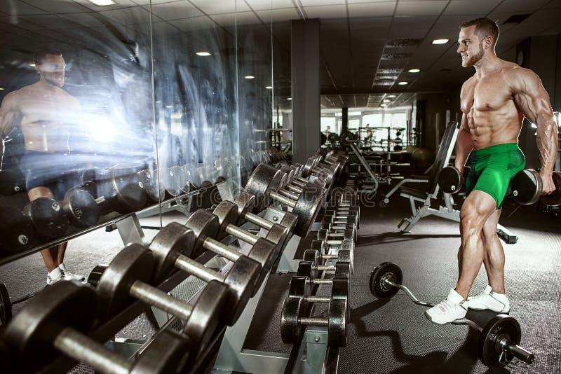 Individuo muscular del culturista que hace ejercicios con pesa de gimnasia foto de archivo libre de regalías