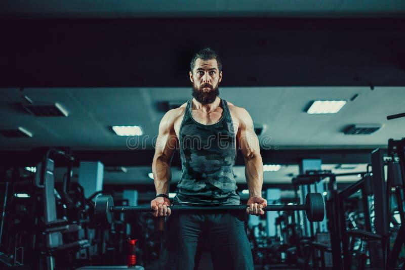 Individuo muscular del culturista que hace ejercicios con pesa de gimnasia en gimnasio foto de archivo