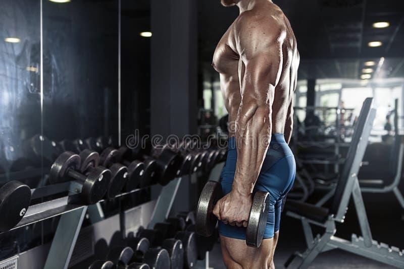 Individuo muscular del culturista que hace ejercicios con pesa de gimnasia grande fotos de archivo libres de regalías