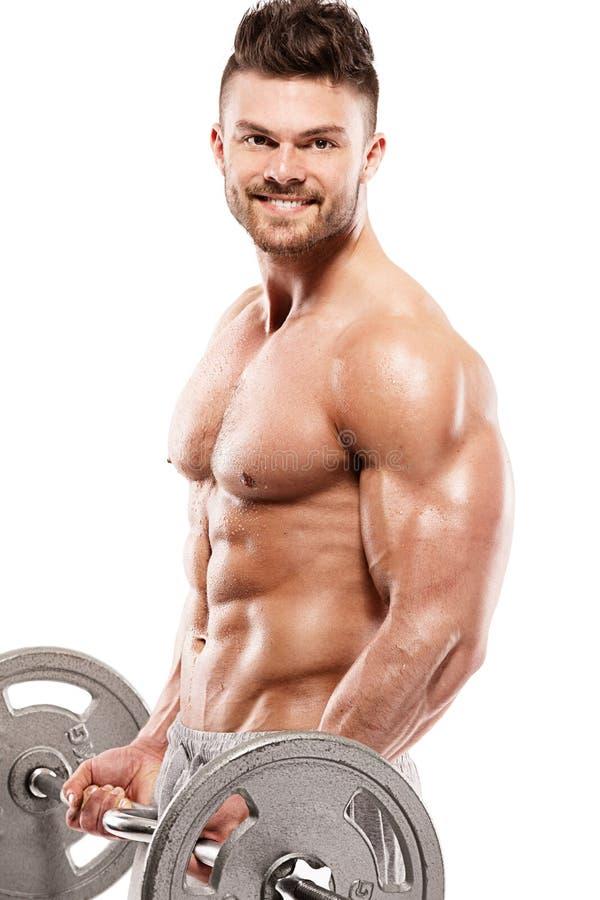 Individuo muscular del culturista que hace ejercicios con pesa de gimnasia grande foto de archivo