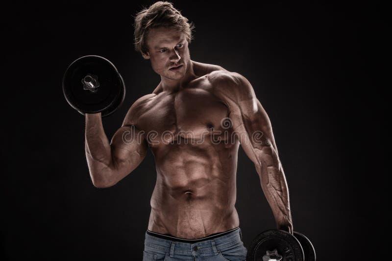 Individuo muscular del culturista que hace ejercicios con pesas de gimnasia imagen de archivo