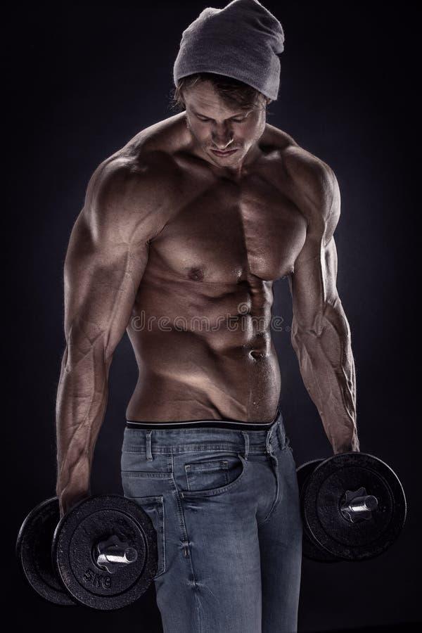 Individuo muscular del culturista que hace ejercicios con pesas de gimnasia foto de archivo